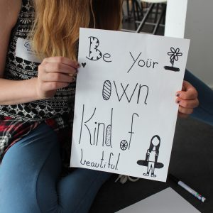 Pige holder skilt med *Be your own kind of beautiful'