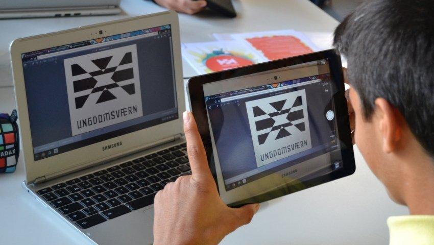 Skoleelev i færd med at affotografere logoet for Ungdomsværn