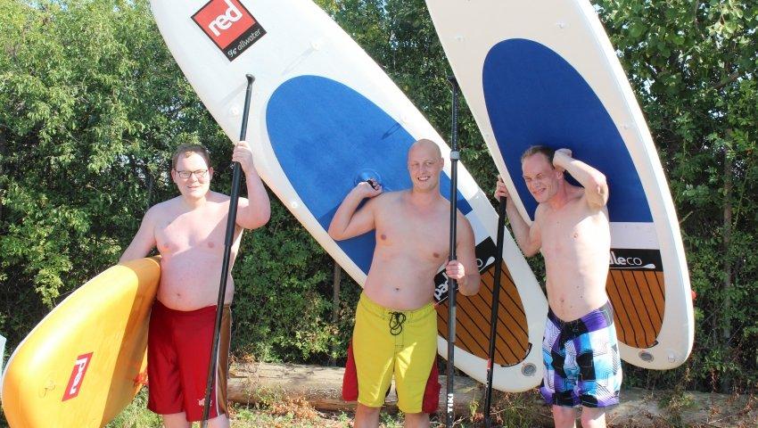 Tre unge drenge med surfboards